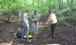 Researchers pull a GPR unit across a hill along a transect to collect data.