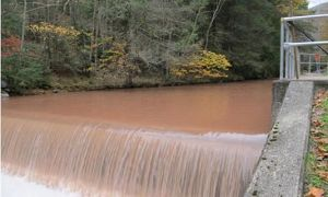 Muddy, brown water rushes down a stream. Image: Brantley, S. (2014, April 9)