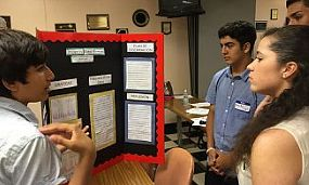 Several students listen to a fellow describe his poster for the data jam.