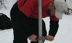 A man, wearing snow shoes, pushes a metal tube deep into the snow.  He is conducting a snow survey and helping measure Snow Water Equivalent (SWE).