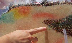 Colorful layers of sand and gravel as viewed through the wall of a small glass demonstration tank. Colorful dye highlights the path of water flow.